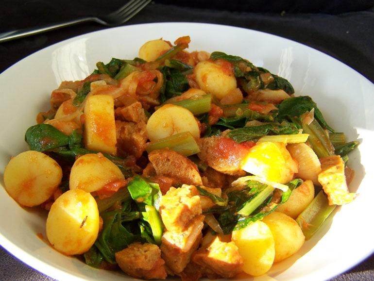 Spinazie-tomatenschotel met vegaworst en aardappeltjes, vegetarisch, veganistisch, plantaardig, zonder zuivel, zonder ei