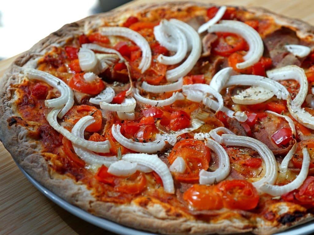 Low budget vegan pizza met tomaat, paprika en ui